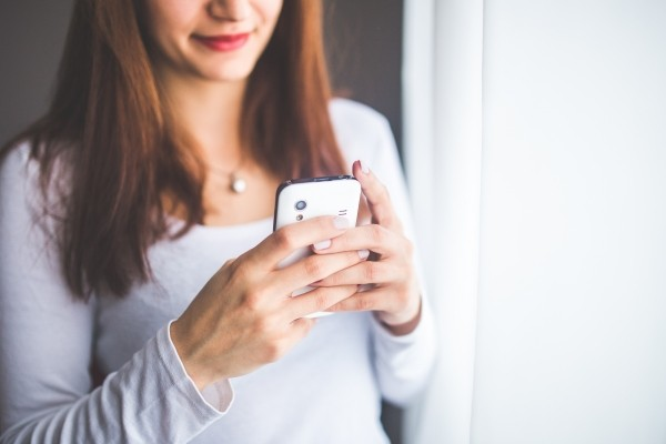 close-up-portrait-of-a-young-woman-typing-a-text-message-on-mobile-phone